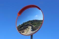 交易显示一条狭窄的街道的镜子反对蓝天 库存图片
