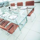 交涉的书桌与准备的财政图和办公设备在事务前的会议室 免版税图库摄影