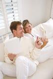 交谈的夫妇读取沙发一起 免版税库存照片