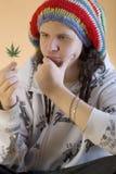 年轻交谈者考虑大麻叶子 图库摄影