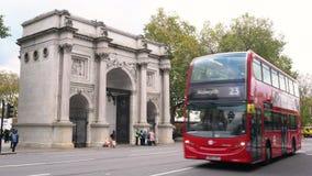 交通、出租汽车和红色双层汽车伦敦公车运送驾驶过去大理石曲拱,牛津街道,海德公园,伦敦 股票视频