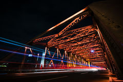 交通光足迹在红色钢桥梁的在晚上 库存照片