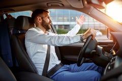 交通堵塞-驾驶汽车的被注重的商人 免版税库存照片