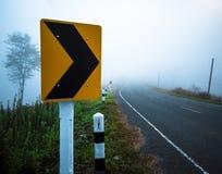 交通标志向右转对薄雾 库存图片