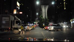 交通警作为车便利在晚上, Sukhumvit路曼谷, 2017年12月13日 股票录像
