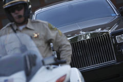 交通警坐有汽车的摩托车在背景中 免版税库存照片