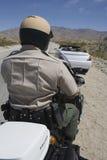 交通警骑马摩托车的背面图 免版税库存照片