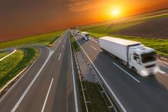 交付在行动迷离的运输卡车在日落的高速公路 免版税库存照片