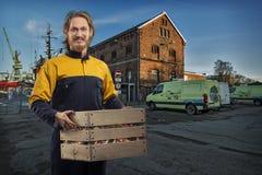 交付或搬家工人人有箱子的在口岸 库存照片