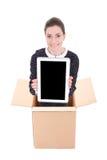 交付-拿着有空白的s的纸板箱的妇女片剂个人计算机 库存图片