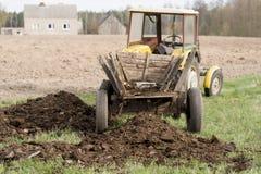 交付肥料的老土气拖拉机。 免版税库存照片