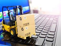 交付,运输或者后勤学的概念 在膝上型计算机的铲车 免版税图库摄影