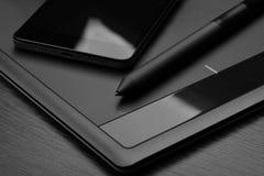 亦称智能手机和图形输入板数字化器或有一支特别象笔一样的铁笔的数字式图画片剂在一个木选项 免版税库存图片