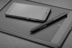 亦称智能手机和图形输入板有一支铁笔的一种数字式图画片剂在一张木桌上 工作场所细节  免版税库存图片