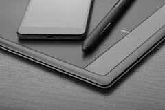 亦称智能手机和数字式艺术上有一支特别象笔一样的铁笔的一个图形输入板在一张木桌上 库存照片