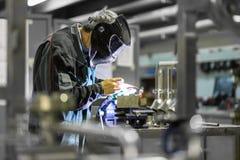 产业工人焊接在金属工厂 免版税库存照片