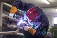 产业工人焊接在金属工厂 免版税库存图片