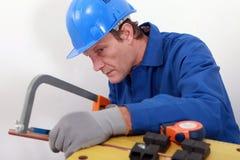产业工人锯切管子 免版税库存图片