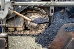 产业工人,使用铁锹的杂物工为运载的沥青在修路 免版税库存照片