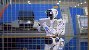 产业机器人,与一台计算机的靠机械装置维持生命的人处理的运作的过程在工厂 股票录像