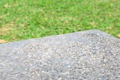 产品立场的岩石桌在前景和绿色领域在背景中 免版税图库摄影