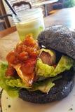 产小羊与蕃茄美味、熔化咸味干乳酪和酥脆烟肉的汉堡在一个木炭小圆面包,与一名绿色圆滑的人 免版税库存照片
