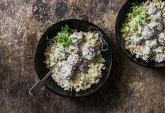 产小羊在酸奶调味汁和碾碎干小麦-在地中海样式的可口健康午餐的丸子在木背景 库存照片