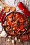 产小羊慢炖与葱、蕃茄和胡椒特写镜头 垂直 库存照片