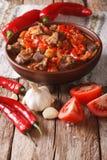 产小羊炖煮的食物用葱、蕃茄和胡椒在碗特写镜头 v 库存图片