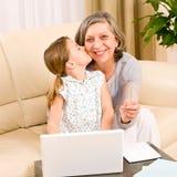 产生亲吻的孙女祖母微笑 免版税库存图片