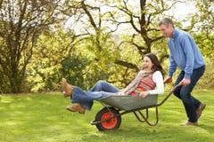 产生人乘驾独轮车妇女的夫妇 免版税库存照片