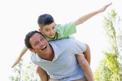 产生人肩扛乘驾微笑的年轻人的男孩 免版税库存图片
