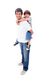 产生他爱的肩扛乘驾儿子的父亲 免版税库存图片