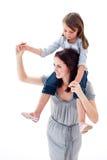 产生她快活的母亲肩扛乘驾的女儿 库存图片