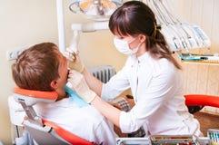 产生她的患者的牙科医生处理年轻人 免版税库存照片