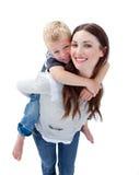 产生她的母亲肩扛乘驾微笑的儿子 免版税图库摄影