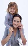 产生她的母亲肩扛乘驾的女儿 图库摄影