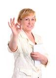 产生好的符号的快乐的成熟女实业家 免版税库存照片