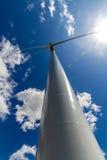 产生干净的金钱的力量的一台巨大的高科技工业风轮机的罕见的平直的特写镜头透视 免版税库存照片