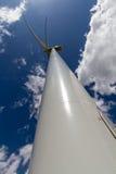 产生干净的金钱的力量的一台巨大的高科技工业风轮机的罕见的晴朗的旁边平直的特写镜头透视 免版税库存图片