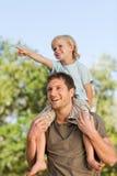 产生愉快的肩扛儿子的父亲 免版税库存照片
