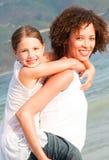 产生母亲肩扛乘驾的海滩女儿 库存图片