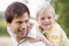 产生的父亲户外扛在肩上乘驾微笑的儿子 免版税库存图片