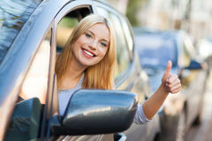 产生赞许的汽车的妇女 免版税库存照片