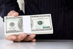 产生货币的生意人 库存照片