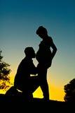 产科夫妇现出轮廓怀孕的妻子的人亲吻的怀孕的腹部 免版税库存照片