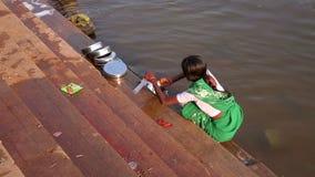 亨比,印度- 2013年4月:地方妇女洗涤的盘在河 股票视频
