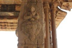 亨比Vittala寺庙柱子雕刻一个邪魔或人Padmasana或莲花坐或思考的姿势的 图库摄影