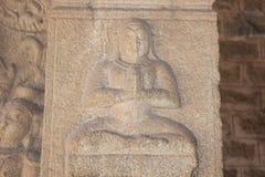 亨比Vittala寺庙柱子雕刻一个邪魔或人Padmasana或莲花坐或思考的姿势的 库存照片