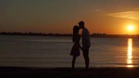 享受一个浪漫日落晚上的爱恋的资深夫妇一起跳舞在被摄制的海滩 股票视频